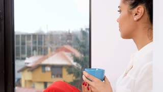 Close up on beautiful woman next to a big window drinking tea or coffee