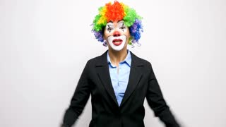 Clown in business suit making silly faces to the camera