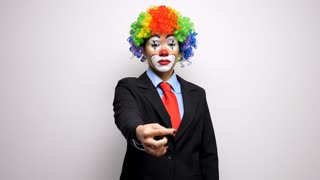 Clown in business suit throwing up a coin in slow motion