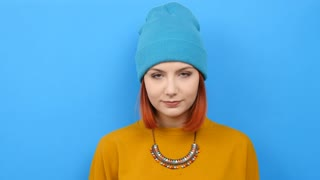Cool beautiful hipster woman poiting up with her finger on blue background