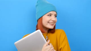 Cool student girl with a laptop in hands on blue background