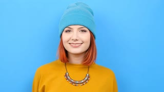 Cool young woman wearing a blue hat and playing with it on blue background