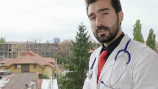 Doctor outside on the balcony talking to the camera. Health care and medicine