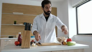 Dollu shot of cook in modern kitchen cutting a squash on wooden table