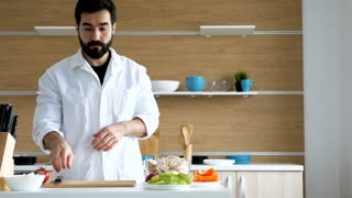 Dolly shot of male cook cutting red onion in modern kitchen