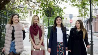 Group of happy girl friends walking in the old part of an city. Friendship and traveling