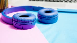 Parallax dolly close up footage of blue wirelled headphones on minimal two colored art desk