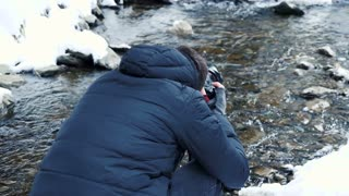 Photographer taking pictures of winter river in mountain. Travel and photography