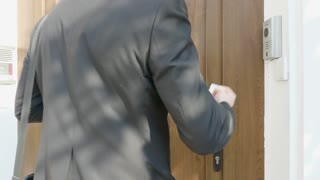 Professional businessman in suit entering the front door of office building and walking on the stairs to his floor. Corporate worker