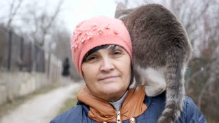 Real woman in her 50s with a cat on her shoulder smiling to the camera in slow motion