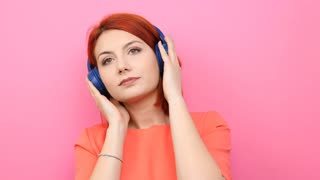 Redhead woman enjoying music in her headset on pink background
