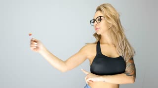Sexy blonde woman making silly faces with a lollipop in hands on gray background in studio