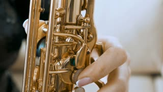 SLOW MOTION close up of woman playing on saxophone. Jazz player rehearsing