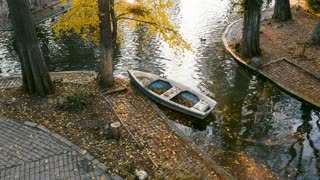 SLOW MOTION. Couple approaching a boat in the autumn park