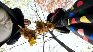 Slow motion low angle of view. Young couple throwing leaves in the park. Romance and love