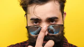 Slow motion of bearded man smiles on yellow background with his sunglasses on