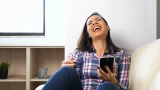 Slow motion of beautiful brunette woman laughing hard with a phone in hands
