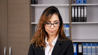Slow motion of brunette businesswoman in office smiling at the camera