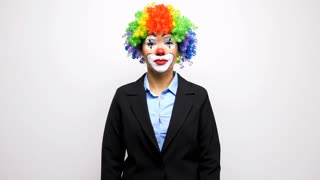 Slow motion of clown in business suit making silly faces to the camera