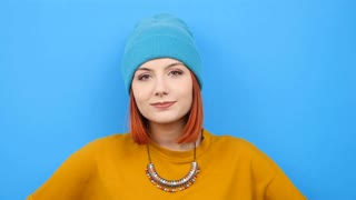 Slow motion of cool hipster woman smiling at the camera on blue background