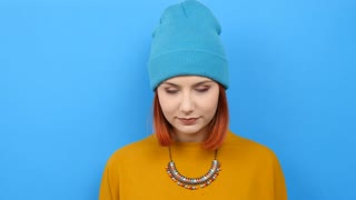 Slow motion of cool young woman in blue hat rise her finger up and then looks up on blue background. Perfect for advertising and commerce