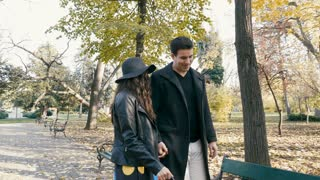 Slow motion of couple walking in the park and sitting on a bench in autumn park. Romance and relationship