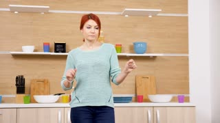 Slow motion of happy and positive woman dances in the kitchen