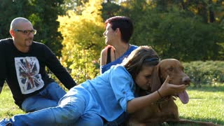 Slow motion of Happy family playing with their dog in the park. Animal lovers