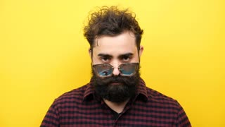 Slow motion of hipster man on yellow background puts his sunglasses on