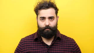 Slow motion of hipster puts his glasses on the face on yellow background