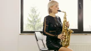 Slow motion of jazz saxophone woman player. She is playing in the living room