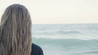 Slow motion of woman from the back looking away at the sea