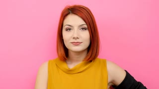 Slow motion of woman in casual clothes smiling large at the camera on pink background
