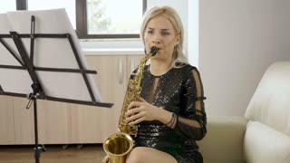 Slow motion of woman playing on saxophone in the living room. Blues player