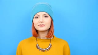 Slow motion of young cool hipster girl wearing a blue hat and playing with it on blue background
