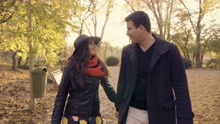 SLOW MOTION of young couple in atumn park walking and laughing. Romance and friendship