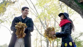 Slow motion of young couple throwing leaves in the park and laughing. Romance and love