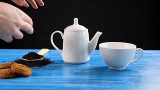 Slow motion on pouring tea in a cup from a kettle