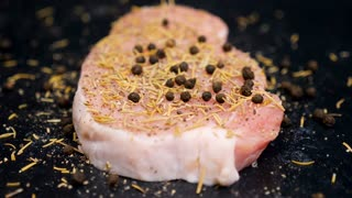 SLOW MOTION. Solt, pepper and spices falling on a piece of raw meat on black wooden background