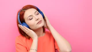 Smiling redhead young woman listening to music in her headset. Pink background
