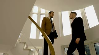 Successful business partners executives shaking hands on the stairs of office building