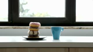 Taking a Cup of coffee and donuts from a plate next to a window. Cozy morning