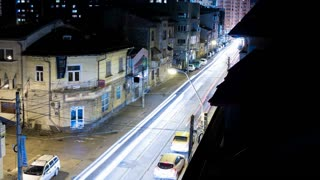 Time lapse of fast moving cars in the night city leaving neon lights in the back from balcony view