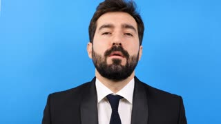 Tired and stressed businessman untying his tie on blue background in front of the camera