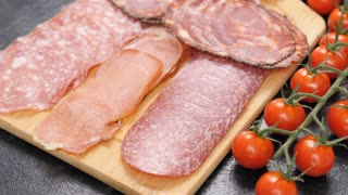 Top view of italian ham next to cherry tomatoes on wooden board