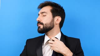 Very tired and stressed businessman starts to bite his tie. Blue background in studio