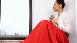 Woman covered with red blanket sitting next to a big window drinking tea or coffee