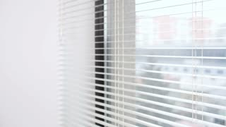Woman looking outside the window through the blinds