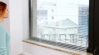 Woman lookis outside the kitchen window through the blinds