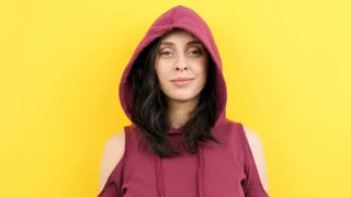 Woman smiling and laughing to the camera while pulling the hood on her face on yellow background. Slow motion